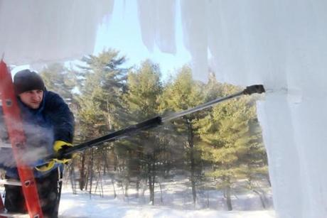 Dmitry Lipinskiy used steam to break off giant icicles on a Carlisle home. Lipinskiy owns Ice Dam Liquidators.